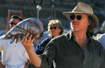 Phil Tippett on set with one of the Brain Bug maquettes for lighting reference.