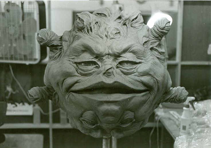 Prop of a floating head; it has a grimaced wrinkly face surrounded by many small eye balls